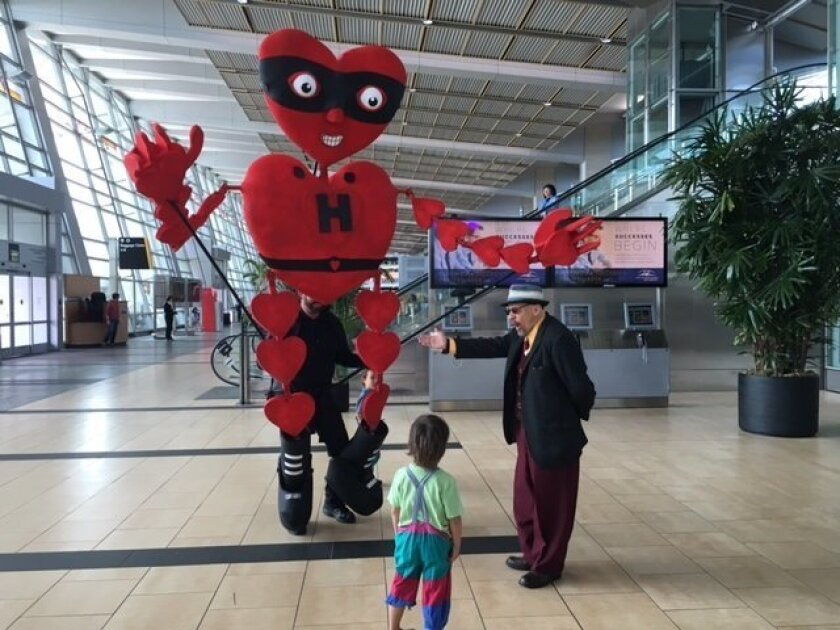 Heartman from the Fern Street Circus greets a boy at Lindbergh Field on Wednesday.