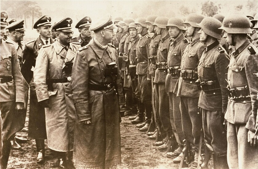 Estimates of the number of former Nazi war criminals who entered the U.S. after World War II range widely from 1,000 to 10,000. Above: Heinrich Himmler, center, head of the Gestapo and the Waffen-SS, reviews troops of the Galician SS-Volunteer Infantry Division of which Michael Karkoc is believed to have been a top commander. The division of Nazi troops is blamed for burning villages filled with women and children.