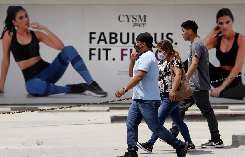 Pedestrians walk past a shuttered gym along Pacific Avenue in Huntington Park on April 29. Gov. Gavin Newsom said he expects to release guidelines in about to week that will allow gyms and fitness studios to reopen.
