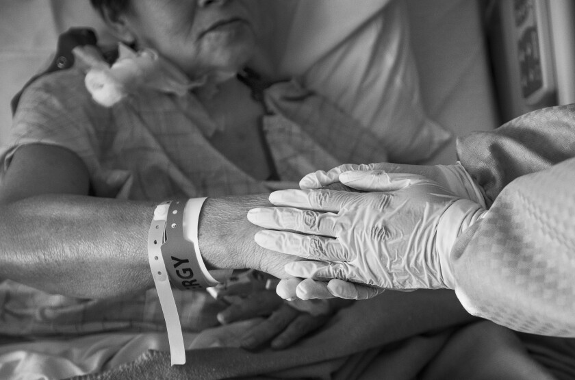 Dr. Maita Kuvhenguhwa, infectious disease specialist at Martin Luther King Jr. Community Hospital, holds Maria Cuellar's hand