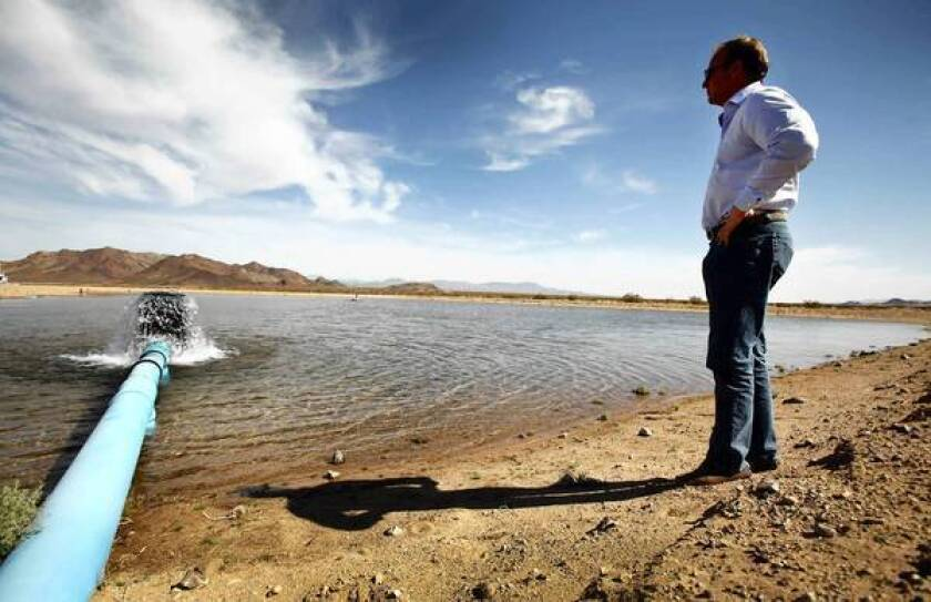 Scott Slater, president and general counsel of Cadiz Inc., watches as water pours into a spreading basin. The basin holds water from a pilot well used for testing. Cadiz Inc. hopes to build a pipeline to export groundwater from the Mojave Desert.