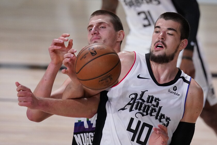Denver Nuggets center Nikola Jokic and Clippers center Ivica Zubac battle for a rebound.