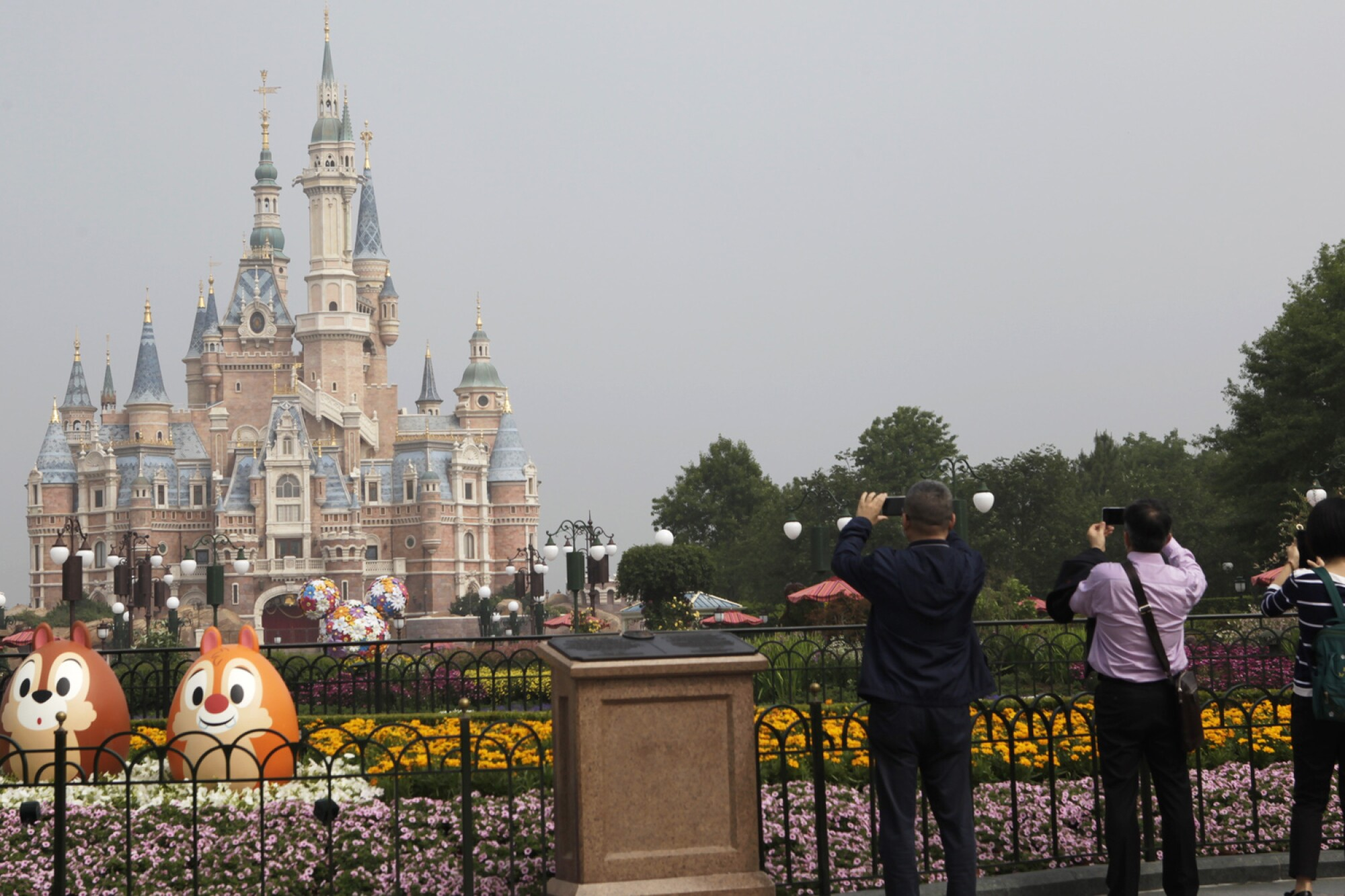 Visitors take photos of Shanghai Disneyland, which reopened on Monday.