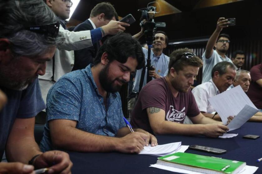 The leader of striking dockworkers in the Chilean port of Valparaiso, Pablo Klimpel, signs an accord to end the walkout during a meeting at the Labor Ministry in Santiago on Friday, Dec. 21. EFE-EPA/Alberto Valdes