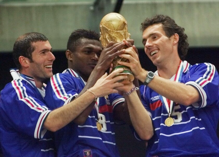FILE - In this Sunday, July 12, 1998 file photo, French teammates from left, Zinedine Zidane, Marcel Desailly and Laurent Blanc hold the soccer World Cup after France defeated Brazil 3-0 in the World Cup final soccer match, at the Stade de France in Saint Denis. On this day, France wins its first World Cup after defeating Brazil 3-0, following 2 headed goals from Zidane and a late strike from Emmanuel Petit. (AP Photo/Michel Euler, File)