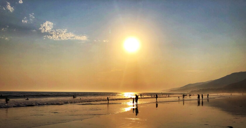 Beachgoers sample the waves at L.A. County's Zuma Beach shortly before sunset on Saturday.
