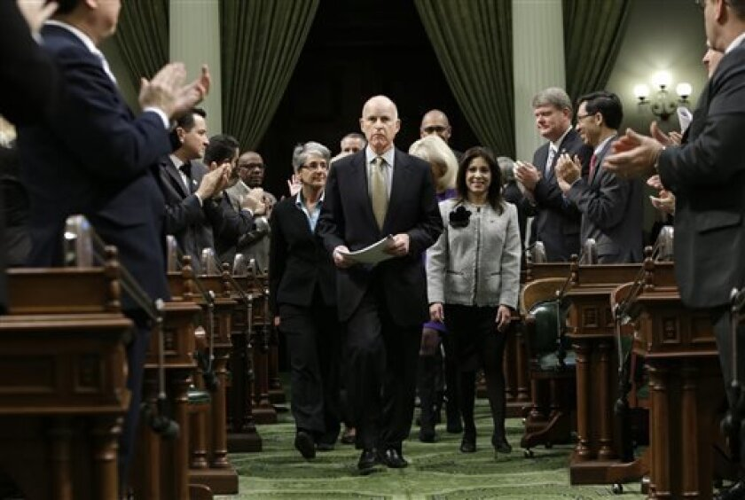FILE - In this Jan. 24, 2013 file photo, lawmakers applaud Gov. Jerry Brown as he enters the Assembly Chambers to give his State of the State address at the Capitol in Sacramento, Calif.  In his second stint as California's chief executive, Brown has received wide praise for bringing the state's ma