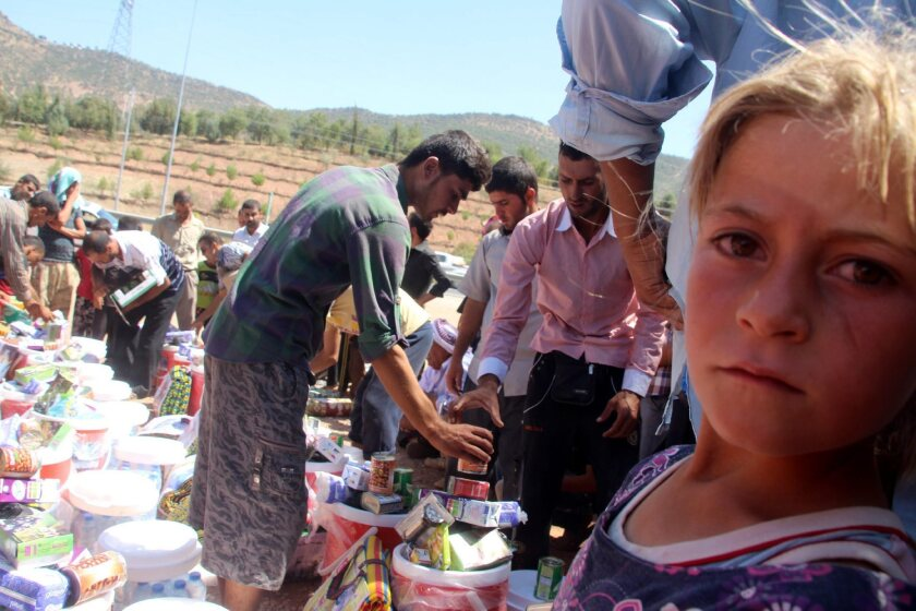 Yazidis who fled advancing Islamic State militants in Mosul receive humanitarian aid near the northern Iraq city of Dohuk on Aug. 21.