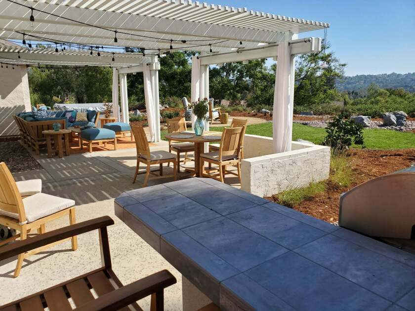 This image provided by John Beaudry shows a yard designed by Nikki Klugh, with an outdoor table that can be used as a desk and outdoor curtain panels to provide privacy and a good Zoom background for work calls. Millions of people found themselves working from home during the past year. And many are likely to continue doing so this summer and beyond, even as pandemic restrictions ease. One bonus when working from home: spending some or all of your work day outside. ( John Beaudry via AP)