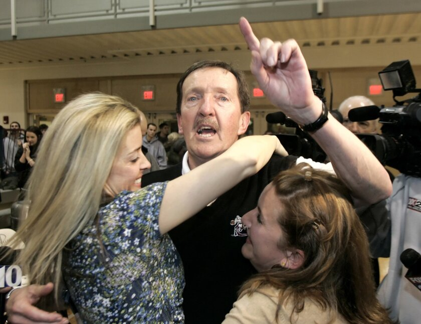 FILE - In this Feb. 1, 2007, file photo, Philadelphia head men's basketball coach Herb Magee, center, celebrates his 829th career coaching victory, a new NCAA Division II record, with his daughters Kay, left, and Eileen, after his team defeated Wilmington College, 65-60, in overtime in Philadelphia