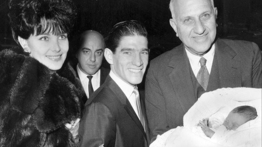 Harry F. Guggenheim, right, holds the newly christened firstborn child of jockey Manuel Ycaza and his then-wife, Linda, in 1963.