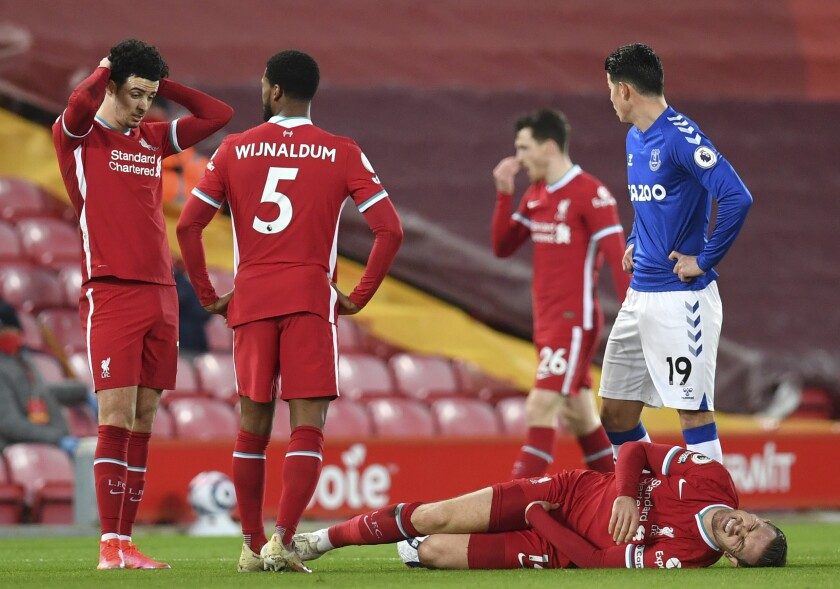 Liverpool's Jordan Henderson lies injured on the ground during the English Premier League soccer match between Liverpool and Everton at Anfield in Liverpool, England, Saturday, Feb. 20, 2021. (Paul Ellis / Pool via AP)