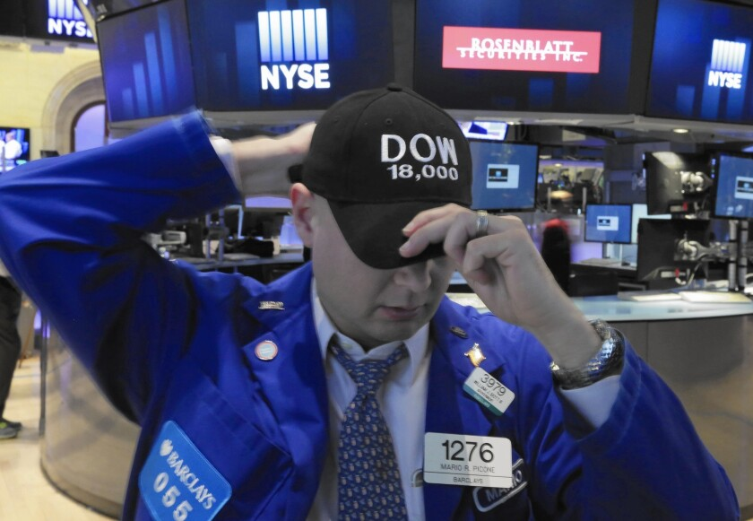 Mario Picone adjusts his Dow 18,000 cap as he works the floor of the New York Stock Exchange.