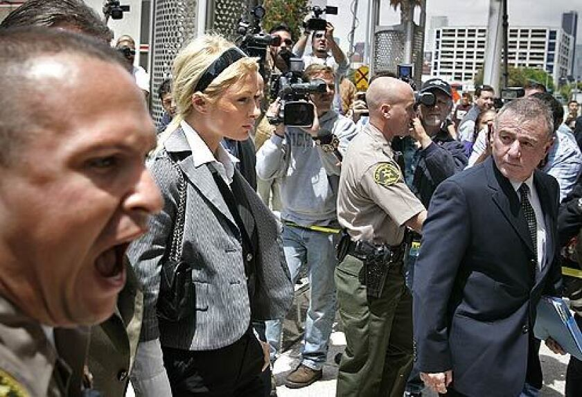 Sheriff's deputies create a wider berth between photographers and Paris Hilton and her lawyer Howard Weitzman.