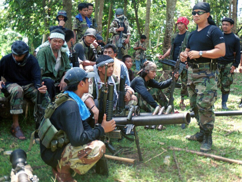 FILE - In this undated file photo, Abu Sayyaf spokesman Abu Sabaya, right foreground, is seen with his band of armed extremists. Philippine troops captured an Abu Sayyaf rebel commander blamed for years of ransom kidnappings and on Sunday, March 21, 2021, rescued the last of his four Indonesian captives, the military said. (AP Photo, File)