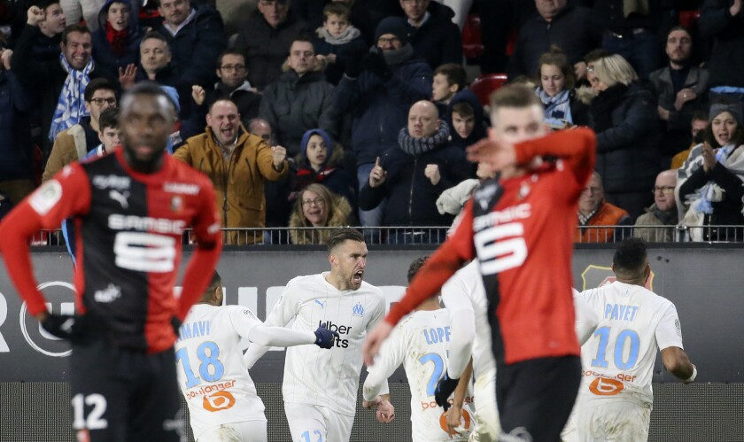 Marseille's Kevin Strootman, center, celebrates with teammates after scoring his side's opening goal during the League One soccer match between Rennes and Marseille, at the Roazhon Park stadium in Rennes, France, Friday, Jan. 10, 2020. (AP Photo/David Vincent)