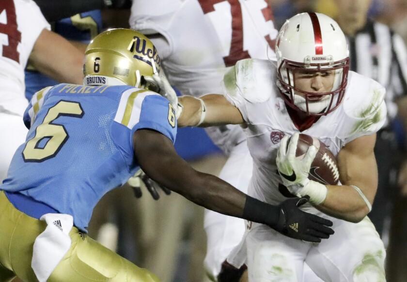 Stanford's Christian McCaffrey runs around UCLA's Adarius Pickett on Sept. 24.