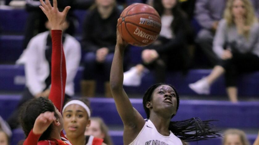 Dee Dee Valenzuela, of San Marcos, shoots for two points. Defending at left is Cathedral's Angelina Roque.
