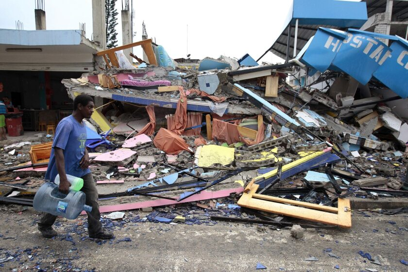 A man walks past the debris of a collapsed building in Pedernales, Ecuador, on Sunday after an earthquake hit the country's northern coastal region. Hundreds have been killed.
