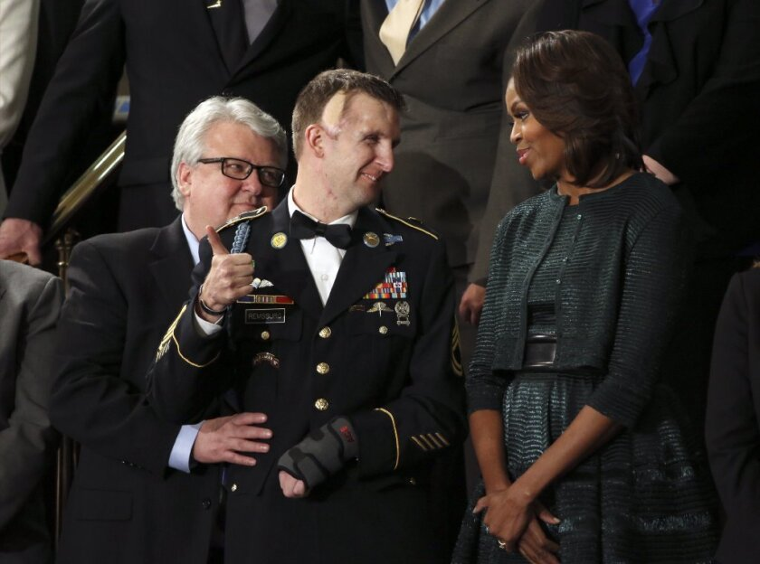 Army Ranger Sgt. First Class Cory Remsburg, center, and his father Craig talk with Michelle Obama in the first lady's box seats before President Barack Obama's State of the Union address on Jan. 28, 2014.