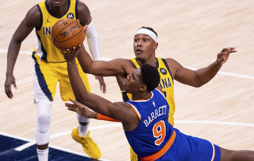 New York Knicks guard RJ Barrett (9) drives a shot to the basket as Indiana Pacers forward Myles Turner (33) tries to block his efforts during the second half of an NBA basketball game in Indianapolis, Saturday, Jan. 2, 2021. (AP Photo/Doug McSchooler)
