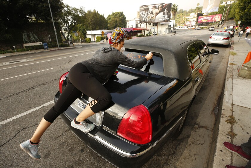 Courtney Banks writes messages on a vehicle window in support of workers who lost their jobs at the Chateau Marmont hotel.
