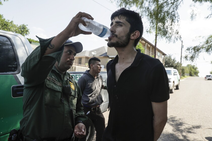 Border Patrol paramedic Roy Ramirez gives water to detainee Juan Carlos Villalobos of Mexico after he and two others were found hiding on a hot afternoon this month in Roma, Texas.