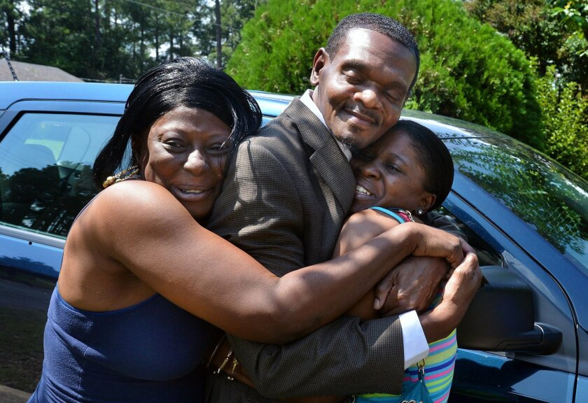 Henry McCollum hugs his cousins as he arrives at his sister's home in Fayetteville, N.C. McCollum and his brother Leon Brown were released after 30 years in prison when DNA evidence cleared them of the rape and murder of an 11-year-old girl in 1983.