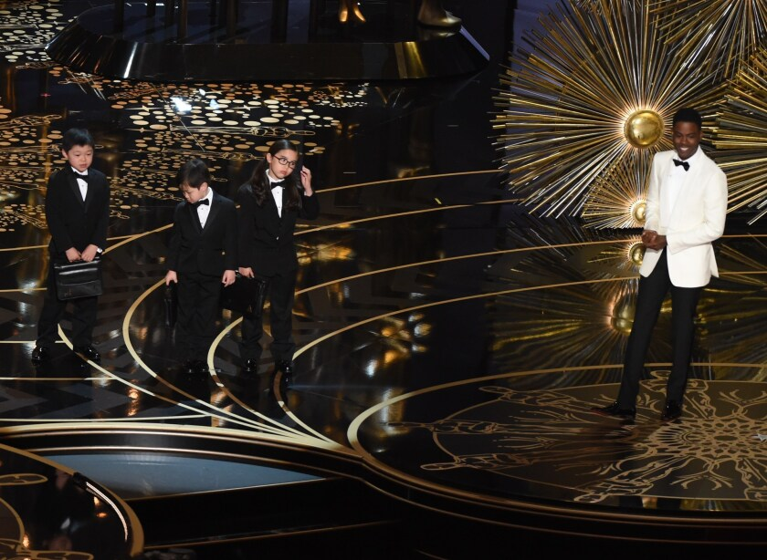 Actor Chris Rock introduces children representing PricewaterhouseCoopers accountants at the 88th Oscars on Sunday.