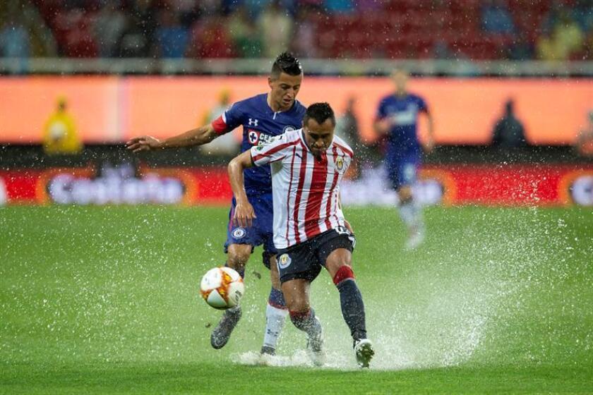 El jugador Edwin Hernández (frente) de Chivas disputa el balón con Roberto Alvarado (atrás) de Cruz Azul durante un partido. EFE/Archivo
