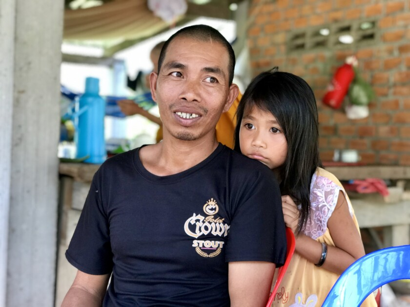 Ros Sitha and his daughter, Siep Vanny, outside their house in Krouch, Cambodia.