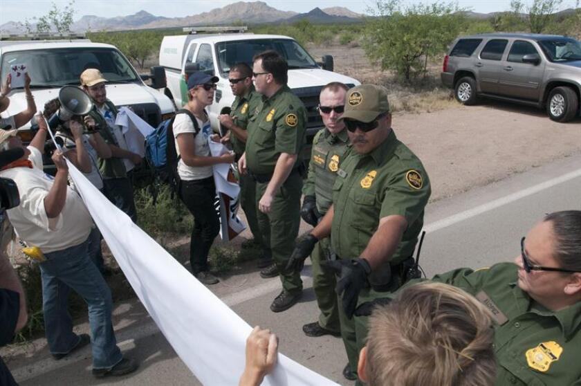 En la imagen, agentes federales vigilan un puesto fronterizo con México ante un grupo de manifestantes.