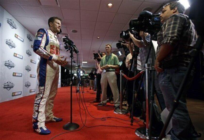 Dale Earnhardt Jr., left, meets with members of the media during NASCAR media day at Daytona International Speedway, Thursday, Feb. 14, 2013, in Daytona Beach, Fla. (AP Photo/John Raoux)