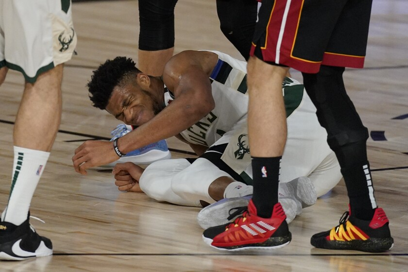 Milwaukee Bucks' Giannis Antetokounmpo (34) falls and injures his ankle slightly but continues to play in the first half of an NBA conference semifinal playoff basketball game against the Miami Heat Friday, Sept. 4, 2020, in Lake Buena Vista, Fla. (AP Photo/Mark J. Terrill)