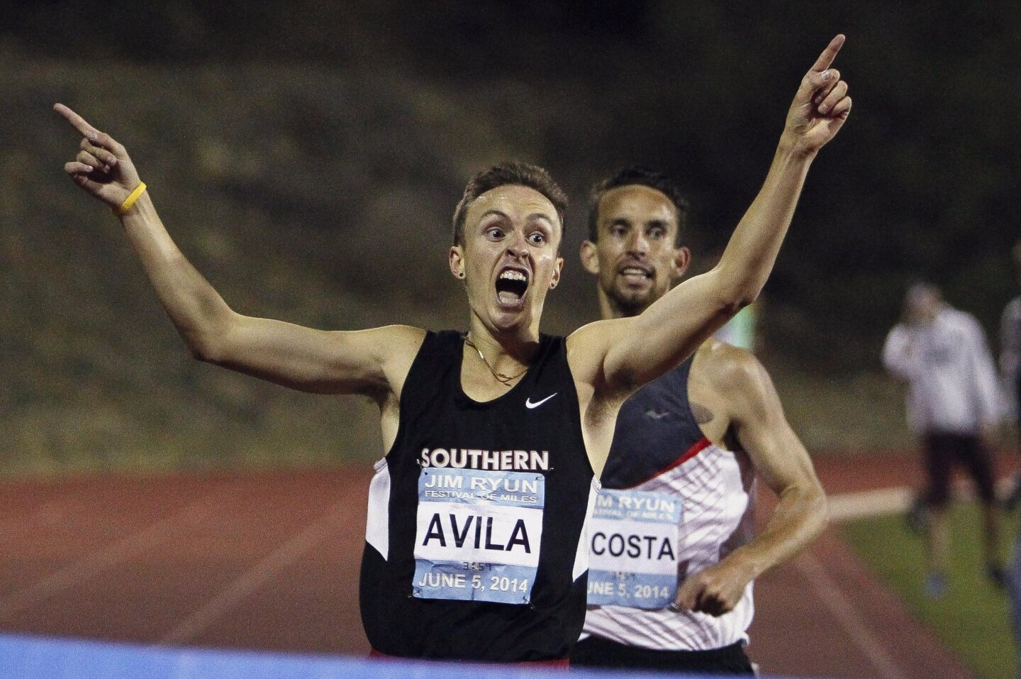 Eric Avila starts to celebrate while he approaches the finish line ahead of AJ Acosta to win the Elite Men's 1 Mile Run during the Jim Ryun Festival of Miles at Balboa Stadium in San Diego.