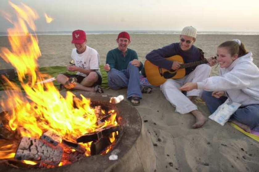 A group of friends hanging out by a fire ring in Newport Beach.
