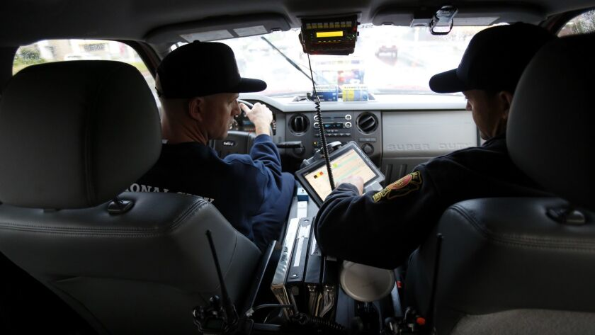 National City firefighter/paramedic Nick Black (left) and Capt. James Stiles cruise in a Ford F-550 pickup in the northeastern section of the city during recent shift. The duo is part of the Fire Departments Squad 33 program, which aims to speed up response times.