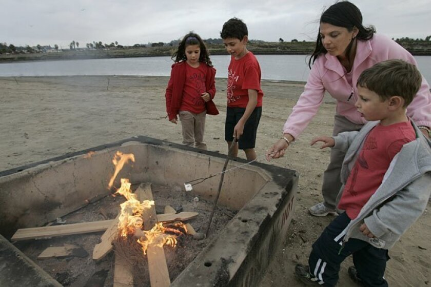 Nanny Jameylee Nuss (second from right) and the Ross family, including (from left) Shayna, 6, Jack, 9, and Sammy, 4,  roast marshmallows in this December 2009 photo.