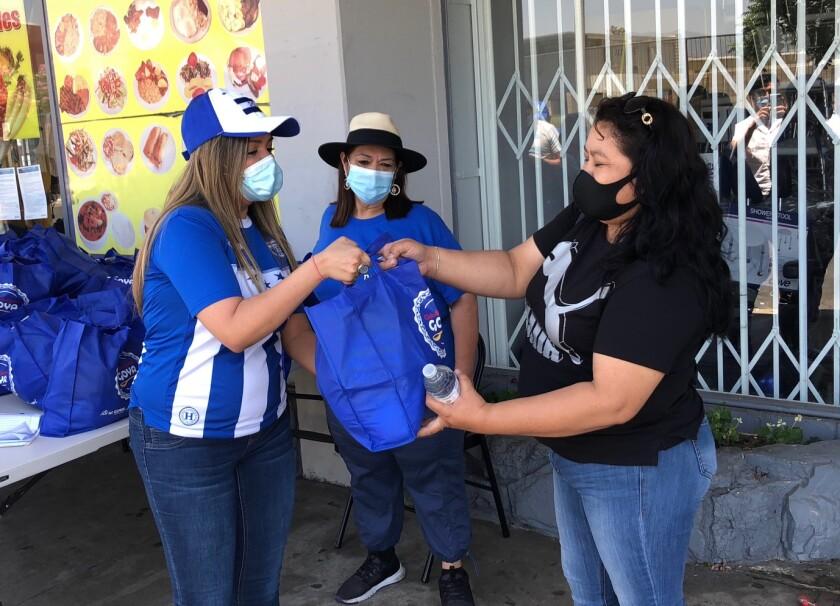 En esta imagen, la cónsul María Fernanda Rivera entrega una ración de comida en el vecindario de North Hollywood.