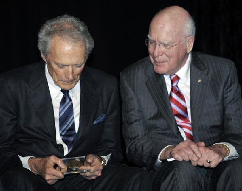 Actor and director Clint Eastwood, left, and Sen. Pat Leahy, D-Vt., look at the James Smithonson Bicentennial Medal which Leahy presented to Eastwood during the opening of the Warner Bros. Theater at the Smithsonian National Museum of American History in Washington, Wednesday, Feb. 1, 2012. (AP Photo/Cliff Owen)