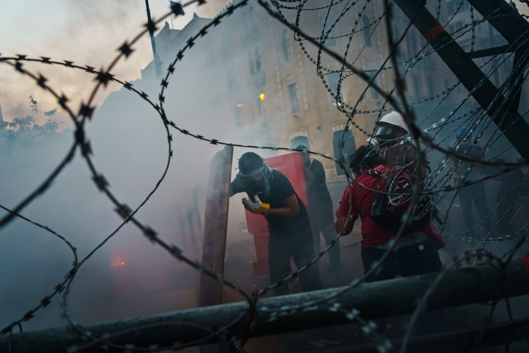Seen through barbed wire, people, some wearing gas masks, stand amid a haze on a city street.
