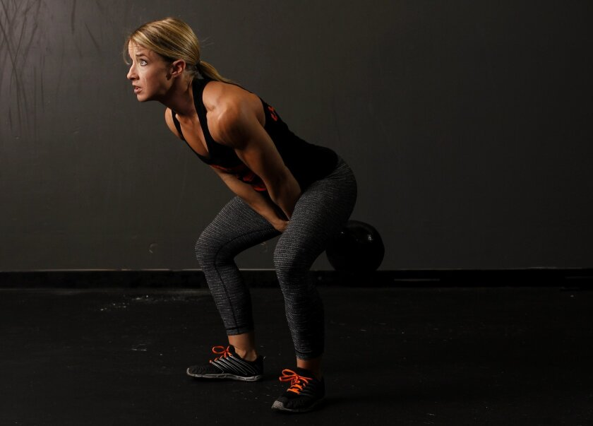 CrossFit coach Nicole Zapoli at Dynamis CrossFit demonstrates a kettle bell swing.