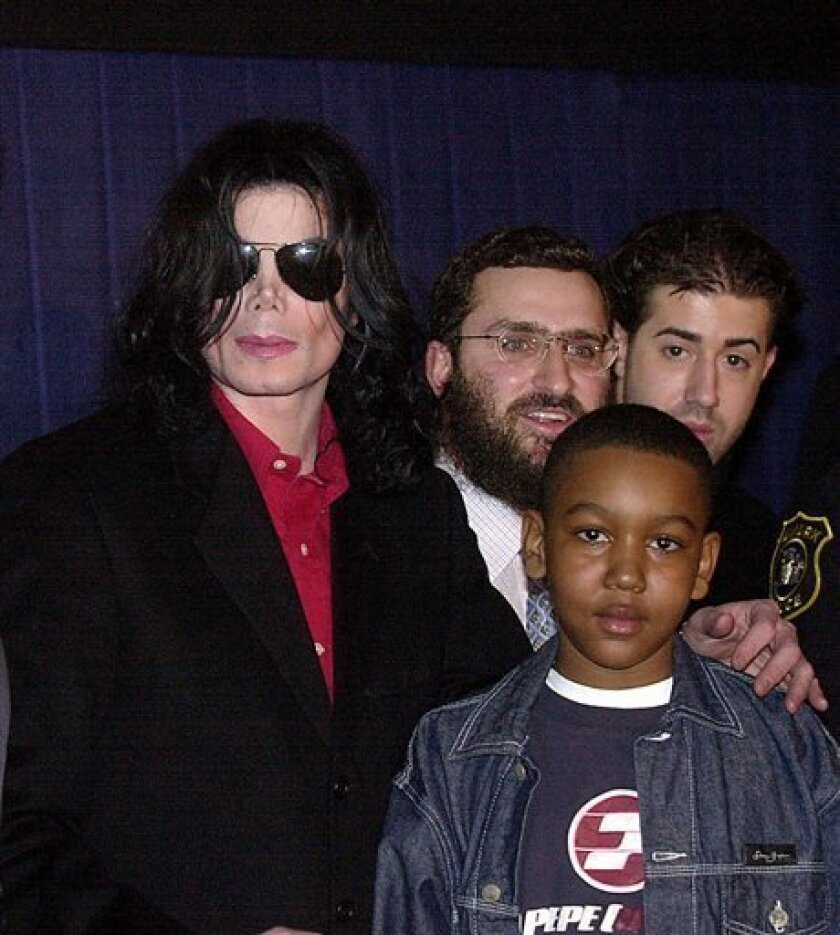 """FILE - In this March 25, 2001 file photograph, pop icon Michael Jackson, center, and Rabbi Schmuley Boteach, pose with a child and an unidentified man at the Loew's Metroplex theatre in Newark, N.J., at the kickoff of Jackson's"""" Heal The Kids"""" program designed to promote quality time between parents and children. A new book, """"The Michael Jackson Tapes,"""" by Boteach, Michael Jackson's former spiritual adviser says the pop superstar feared the ravages of old age and appeared to be abusing prescription drugs and cosmetic surgery nearly a decade before his death. (AP Photo/Warren Westura, File)"""