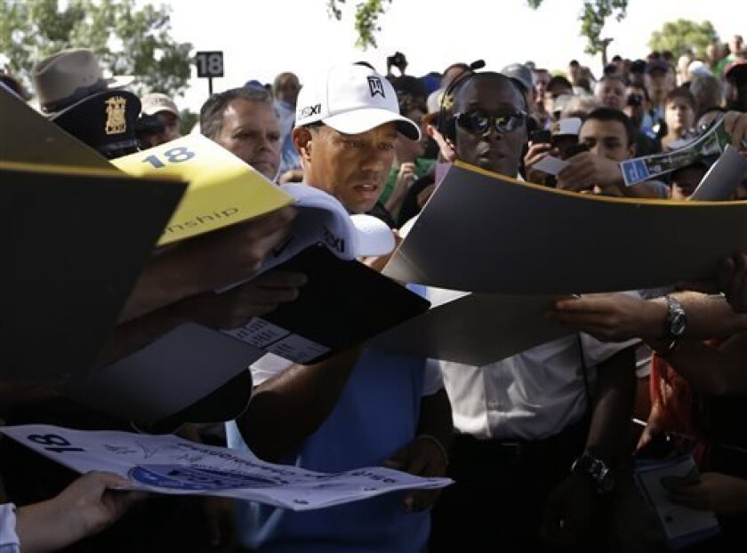 Tiger Woods signs autographs during a practice round for the PGA Championship golf tournament at Oak Hill Country Club, Tuesday, Aug. 6, 2013, in Pittsford, N.Y. (AP Photo/Charlie Neibergall)