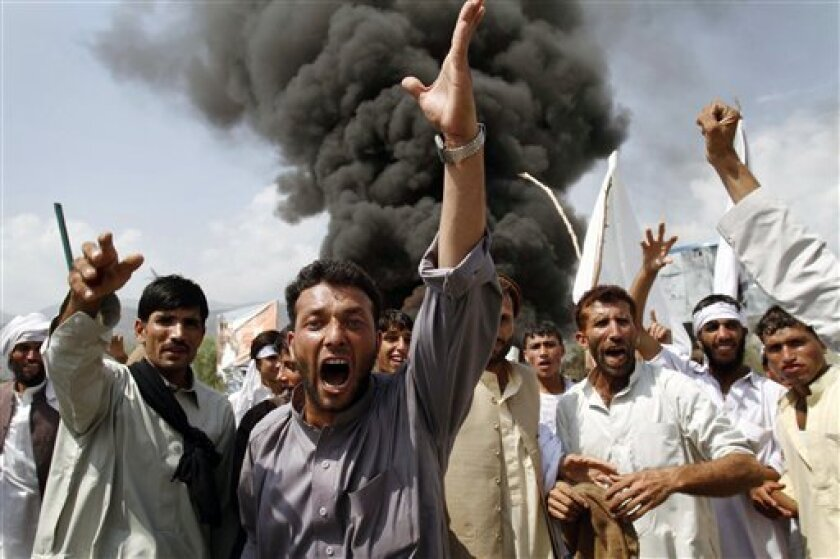 Afghans shout anti-U.S. slogans as they burn tires and block a highway during a protest in reaction to a small American church's plan to burn copies of the Quran, at Jalalabad, east of Kabul, Afghanistan, Friday, Sept. 10, 2010. Religious and political leaders across the Muslim world welcomed a decision by the church to suspend its plans to torch copies of their holy book but some said Friday the damage has already been done. (AP Photo/Rahmat Gul)