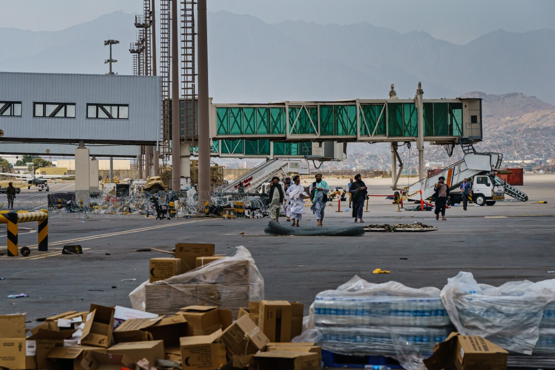 Taliban fighters walk toward stacks of bottled water and other supplies left on the tarmac at the Kabul airport