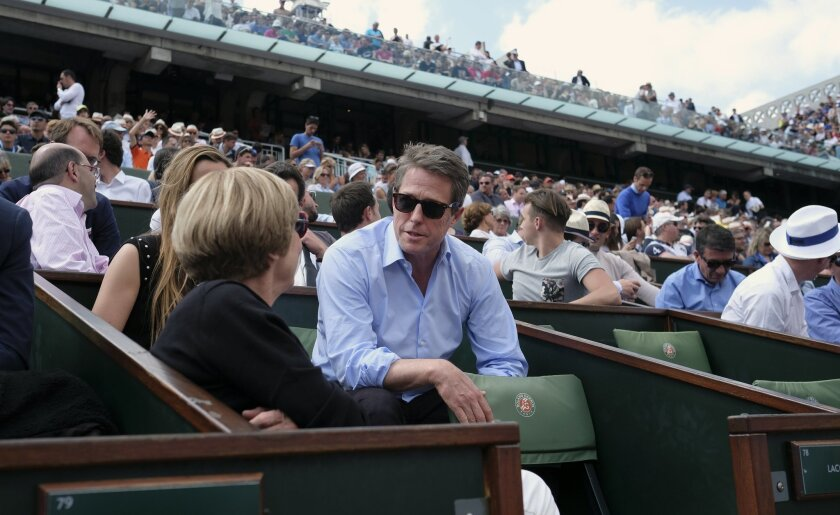 British actor Hugh Grant, center, watches Andy Murray in his second round match of the French Open tennis tournament against France's Mathias Bourgue at the Roland Garros stadium in Paris, France, Wednesday, May 25, 2016. (AP Photo/Alastair Grant)