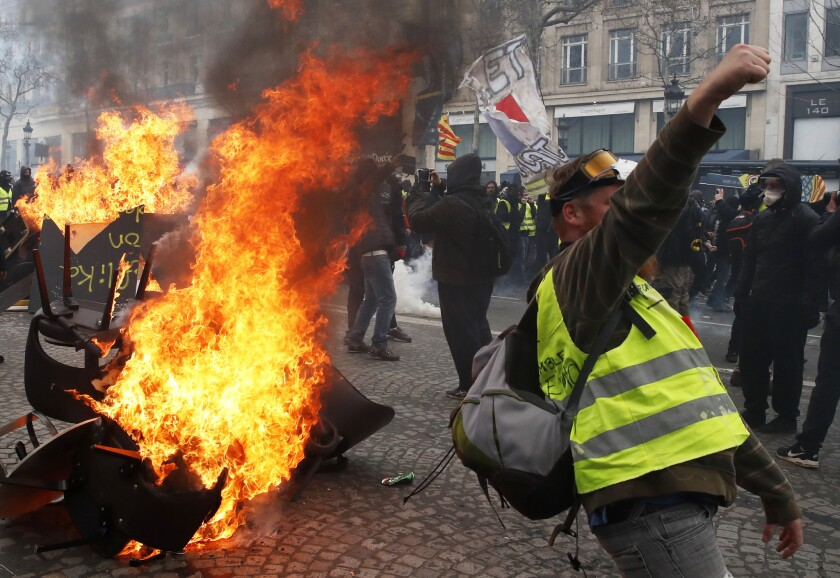 """Un manifestante corea lemas delante de una barricada en llamas durante una protesta del movimiento de los """"chalecos amarillos"""" en París, el 16 de marzo de 2019. (AP Foto/Christophe Ena)"""
