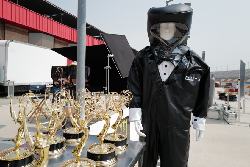 A mannequin in a tuxedo hazmat suit guards the Emmy statuettes in preparation for the 72nd Emmy Awards Sunday.
