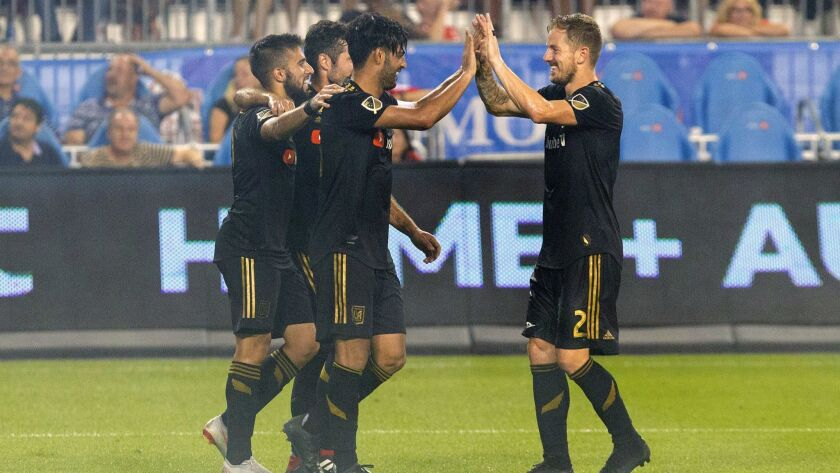 LAFC's Carlos Vela, left, is congratulated by Jordan Harvey after scoring his team's fourth goal against Toronto FC during the second half on Sept. 1 in Toronto.